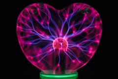 Plasma ball heart glowing in the dark - stock photo