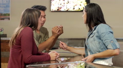 Customers at a marijuana shop being shown a small glass pipe Stock Footage