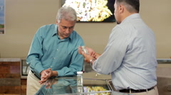 Older customer at marijuana shop looking closely at product and smelling it Stock Footage