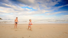 Kids Girl with Pigtail Boy Throw Catch Ball on Sand Beach Stock Footage