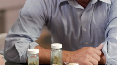 Close up of an associate in marijuana shop showing products to customers - stock footage