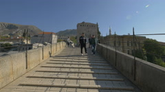 People walking and a couple taking pictures on Stari Most in Mostar Stock Footage