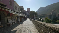 Street with shops near the river and the Old Bridge in Mostar Stock Footage