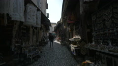 A backpacker and a woman on a street with souvenir shops in Mostar Stock Footage