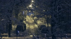 Cars moving at night lit avenue with snow Stock Footage