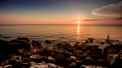 Stone Beach Fisherman Silhouette at Sunset against sky Stock Footage