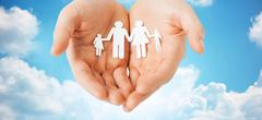 Stock Photo of man hands holding paper cutout of family