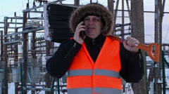 Electrician with smart phone and snow shovel at power plant in winter Stock Footage