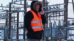 Electrician talking on smart phone at power plant in winter Stock Footage