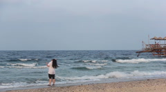 Woman standing on the beach and straightens hair Stock Footage
