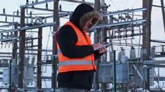 Electrician with tablet PC at power plant in winter - stock footage