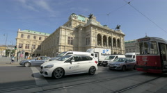 Cars driving and people walking on Opernring street near the Opera in Vienna Stock Footage