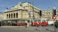 People walking, cars and trams driving in front of the Opera in Vienna Stock Footage