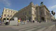 People walking and biking and cars driving near the opera in Vienna Stock Footage