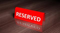 Red glossy reservation sign on wooden surface with reflection Stock Photos