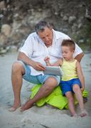 Grandfather and grandchild using pad on the beach - stock photo