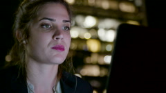 Business woman sitting in a cafe at night, working on a laptop computer Stock Footage