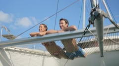 Couple suntanning on a catamaran net - stock footage