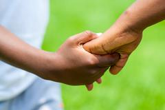 Detail of African boy holding girls hand. - stock photo