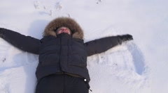 Man doing angel figure in the snow Stock Footage