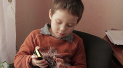 Ittle boy playing a game on your smartphone Stock Footage