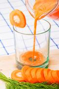 Filling a glass of fresh carrot juice from  pitcher Stock Photos