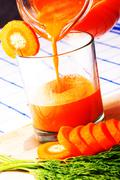 filling a glass of fresh carrot juice from  pitcher - stock photo