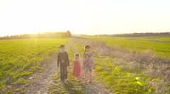Stock Video Footage of Steady Cam shot of three kids walking on a gravel road during sunset