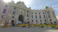 Stock Video Footage of People sitting on ground in front of the beautiful Hofburg Palace, Vienna
