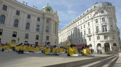 Stock Video Footage of People with yellow T-shirts sitting down in front of Hofburg Palace in Vienna