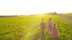 Steady Cam shot of three kids running in a field during sunset - stock footage