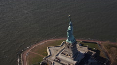 Over Liberty Island, rear view of Statue of Liberty with sun glare on the water. Stock Footage