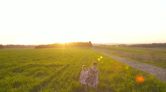 Stock Video Footage of Steady Cam shot of two girls running in a field during sunset