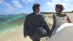 Just married couple running on a caribbean beach Stock Footage