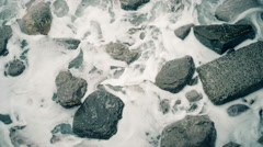 Viewed from above Sea waves crashes on to the rocks. White foam covers the rocks Stock Footage