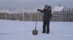 Man digging snow with a shovel in a winter garden Stock Footage