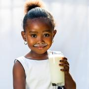 Cute african girl drinking glass of milk. - stock photo