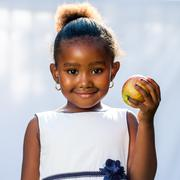 Cute african girl holding apple. - stock photo