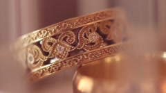 Macro of the golden bridal rings with diamonds on blurred pastel background Stock Footage