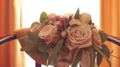 Bridal bouquet with long tape in high glass vase on pastel background, close up Stock Footage