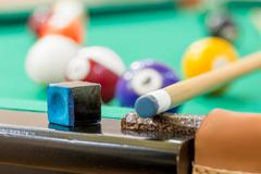 chalk and cue on the edge of the table of billiard close-up - stock photo