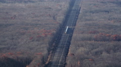 Aerial shot of a train moving through fields and next to a housing complex. Shot Stock Footage