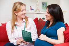 Midwife Discussing Literature With Pregnant Woman During Home Vi - stock photo