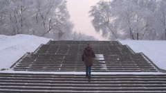 Woman running up the stairs in winter Stock Footage
