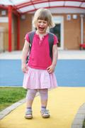 Stock Photo of Little Crying Girl Standing Outside Pre School Building