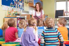 Group Of Pre School Children Listening To Teacher Reading Story Stock Photos