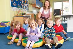 Class Of Pre School Children At Story Time With Teacher Stock Photos