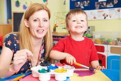 Teacher Helping Preschool Child In Art Class - stock photo
