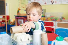 Boy Building Junk Model In Pre School Class Stock Photos