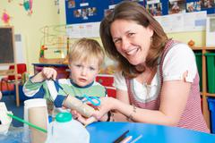 Teacher Helping Little Boy To Build Model In Art Class - stock photo